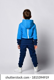 Fashion boy posing wearing warm blue black sports tracksuit and snickers. Full length isolated studio portrait on gray background back view. Child sport clothing shop promotion