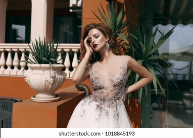 Fashion bride in gorgeous wedding dress outdoor spring portrait. Beautiful model girl with bridal makeup and hairstyle in marriage lace dress. Luxury fashion wedding dress on beauty lady,palms,Italy
