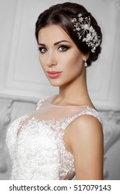 Fashion bride in gorgeous wedding dress studio portrait. Beautiful model with bridal makeup and hairstyle in marriage lace dress.