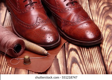Fashion brogues shoes handmade and shoemaker tools hammer, awl, nails, skien of thread .Wooden background.Concept cobbler tools.copy space