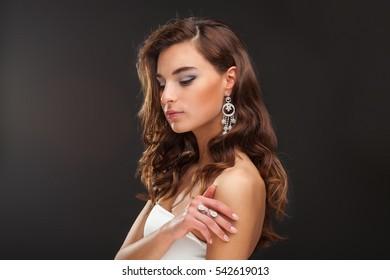 Fashion Brunette Model Portrait. Jewelry and Hairstyle. Elegant lady on black background.
