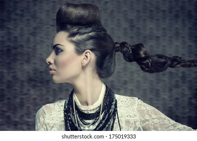 fashion brunette woman turned on profile in close-up portrait with creative hairdo and strong make-up. Wearing white lace shirt and a lot of necklaces