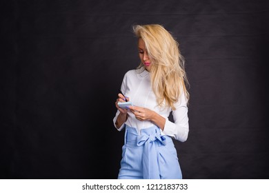 Fashion, business and people concept - Cute blond woman in jeans writes notes on stickers over black background with copy space