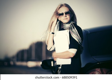 Fashion business woman with financial papers next to her car. Stylish female model in sunglasses outdoor