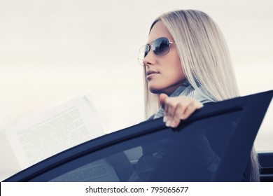 Fashion business woman with financial papers outside a her car Stylish blond female model in sunglasses