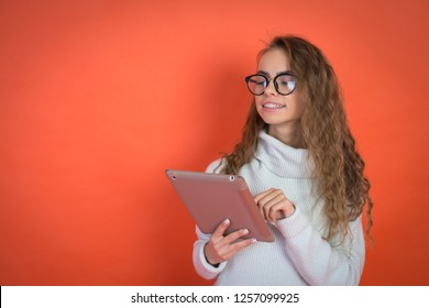 Fashion business woman with glasses portrait, holding a tablet in his hands, red background, copyspace