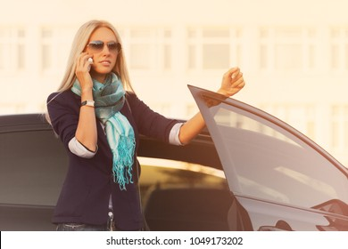 Fashion business woman talking on cell phone outside a car Stylish female model wearing sunglasses and dark blue blazer