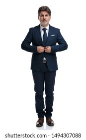 Fashion businessman unbuttoning his jacket and looking forward while wearing a blue suit and tie, standing on white studio background