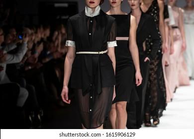Fashion catwalk runway event, model walking the show finale. Fashion week themed photograph.