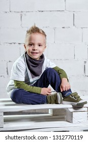 Fashion child model. Portrait little kid in fashionable casual clothes. Cute stylish boy sitting on pallets. handsome blond caucasian kid.