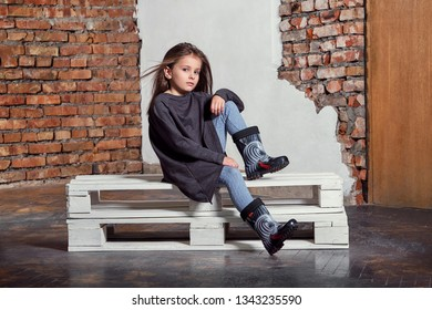 Fashion child posing sitting on pallets near brick wall. High fashion portrait of little girl. Attractive kid model in stylish, casual clothes, sweater, gumboots.