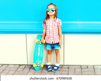 Fashion child with skateboard in the city on a colorful blue background