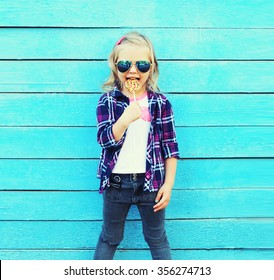 Fashion child with sweet caramel lollipop having fun over colorful blue background