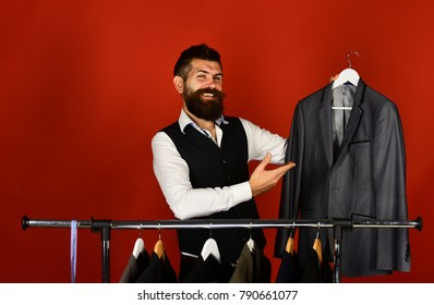 Fashion choice concept. Man with beard in vest by clothes rack. Designer presents his work near clothes hangers. Tailor with happy face holds grey suit near custom jackets on red background.