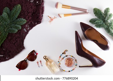 Fashion Christmas flat lay frame. Dress, hight heel shoes and evergreen tree twig, dressing up for Christmas party fashion accessoires frame