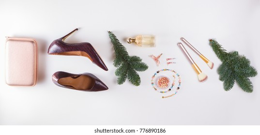 Fashion Christmas flat lay scene. Hight heel shoes, bag, evergreen tree twig, dressing up for Christmas party fashion accessoires.
