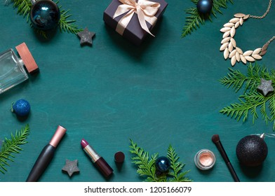 Fashion Christmas New Year flat lay on the wooden turquoise background with cosmetics and accessories. Top view concept winter holiday beauty frame. Copy space