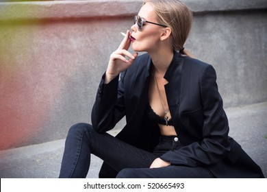 Fashion close up Fine art portrait of a beautiful Elegant lady with cigarette.Sexy blonde woman in sunglasses and casual black jacket smoking cigarette.woman smoking a cigarette, thinking.Looking away