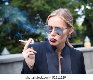 Fashion close up Fine art portrait of a beautiful Elegant lady with cigarette.Sexy blonde woman in sunglasses and casual black jacket smoking cigarette. Urban background, not isolated.Sexy woman.