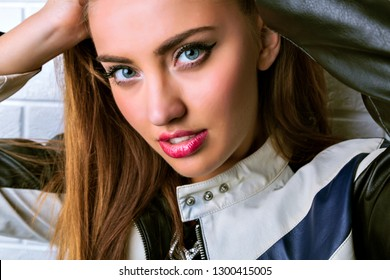 Fashion close up portrait of amazing stylish woman with perfect face, big blue eyes and seductive full lips, wearing racer leather jacket and lookin on camera.