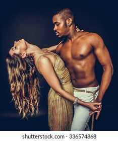 Fashion close up portrait of attractive dancing couple in sensual hugs. Holding hands. Dancing latino. Passion Love.  The girl's perfect skin facial make-up. The guy's pumped abs. Gold toned colors