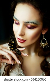 Fashion close portrait of the bride with a bright, fashionable make-up with lots of sequins and burgundy lipstick that holds a butterfly with black and yellow wings on her arm