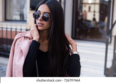 Fashion close up portrait of pretty stylish woman in fall casual outfit walking in city. Street style.young beautiful stylish woman walking in street in pink coat,autumn fashion trend.
