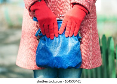 A fashion close up of a woman in a red spring-autumn wool topcoat, blue jeans and red gloves. Woman is holding a blue leather bag in her hands. On the background you can notice a green fence