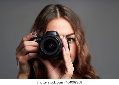 fashion close-up portrait of beautiful girl with camera.Pretty woman is a professional photographer with dslr camera