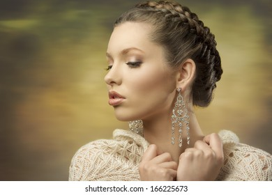 fashion close-up portrait of elegant female posing with classic hair-style, precious earrings and wool shawl
