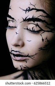 Fashion close-up portrait of model female with a amazing creative make-up. Closed eyes. Painted muah silhouettes of trees and birds. Calm face, halloween.