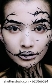 Fashion close-up portrait of model female with a amazing creative make-up. Open eyes. Painted muah silhouettes of trees and birds. Calm face, halloween.