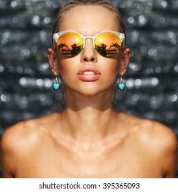 Fashion closeup portrait of young seductive woman in sunglasses