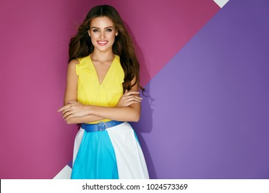 Fashion Clothes. Beautiful Girl In Fashionable Summer Dress. Portrait Of Happy Gorgeous Woman With Beauty Face Makeup And Long Curly Hair On Stylish Colorful Background. Style Look. High Resolution.