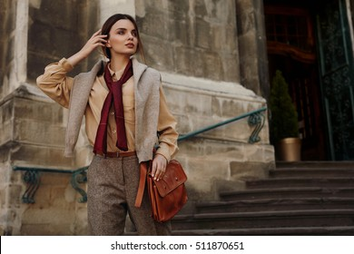 Fashion Clothes. Beautiful Sexy Woman Wearing High Fashionable Spring, Fall Clothing ( Shirt, Scarf, Pants, Sweater, Leather Bag ) Outdoors. Female Model In Trendy Outfit Posing In The Street