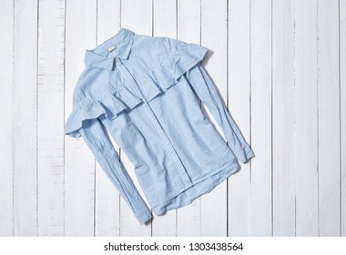 Fashion clothes. Blue and white striped shirt with flounce on white wooden floor planks