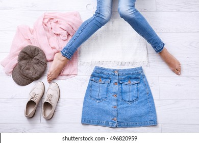 Fashion clothes with different accessories and female legs in jeans on white wooden background. Top view and copy space.
