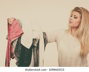 Fashion, clothes dilemmas concept. Young blonde woman teen girl holding big pile of warm winter clothing, cant decide what to wear, toned image
