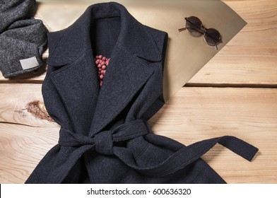 Fashion clothes on clothing rack - bright colorful closet. Composition of woman's fashion look on wooden background. Top view of fashion coat and sunglasses