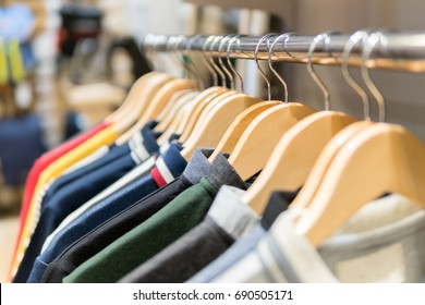 Fashion clothes on clothing rack - bright colorful closet. Closeup of rainbow color choice of trendy male wear on hangers in store closet
