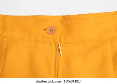 Fashion clothes. Part of orange mini skirt, button and zipper.