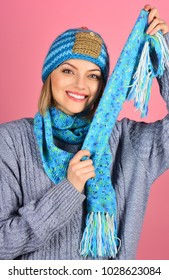 Fashion clothes. Smiling woman holds scarf in hands. Isolated on pink background. People concept. Autumn winter fashion.