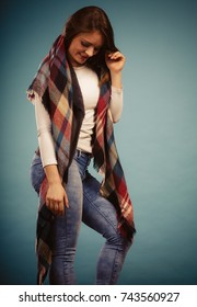 Fashion clothing concept. Beautiful model posing at studio. Girl is wearing denim trousers and checkered scarf.