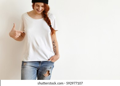 Fashion and clothing design concept. Cheerful happy young female with ginger hair and tattoo looking down and pointing index finger at copy space on her white oversize t-shirt, smiling joyfully