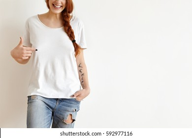 Fashion, clothing and design concept. Cropped portrait of attractive redhead European teenager with tatoo, smiling cheerfully, pointing finger at copy space on her stylish white oversize t-shirt