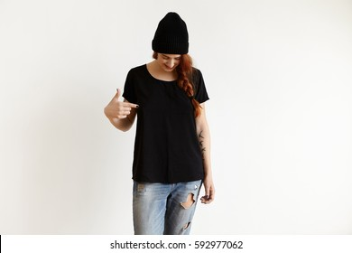 Fashion, clothing and design concept. Studio shot of fashionable Caucasian girl in stylish hat and ragged blue jeans, looking down and pointing index finger at copy space on her black loose t-shirt