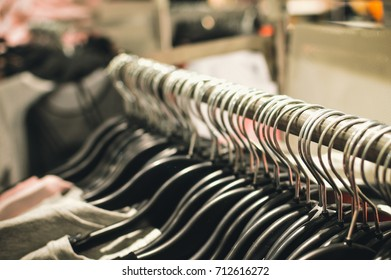 Fashion clothing hanging on hangers. Closeup on group of accessory, household showroom department