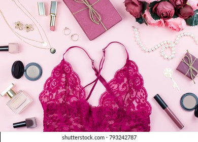Fashion collection with sexy red lace lingerie, accessories, flowers, cosmetics and jewelry on pink background, copyspace. Womens Day concept