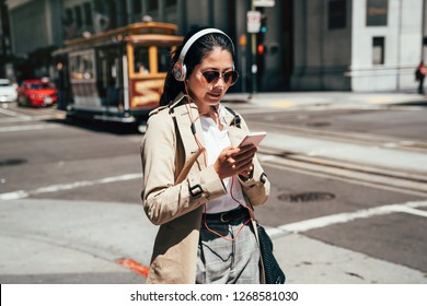 fashion college girl listening music with headphones and smart phone online walking on street in san francisco with cable car driving through. student in sunglasses using cellphone streetcar in back.