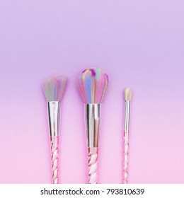 fashion colored makeup brushes on a gradient pink and purple background. pastel flat lay